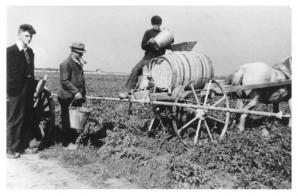 Beeldbank Wieringermeer. Schelpenbolweg, familie Punter aan de slag met de sproeimachine, anno 1940.